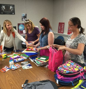 Lynn McCollough, Diane Webster, Nicole Lauzon and Michele Giovine, all CMA staff members, stuff backpacks with school supplies for children to be distributed through One Simple Wish.